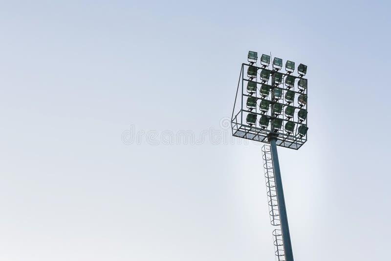 Grandes projetores exteriores altos altos do estádio na construção rígida do quadro sob a luz solar natural foto de stock royalty free