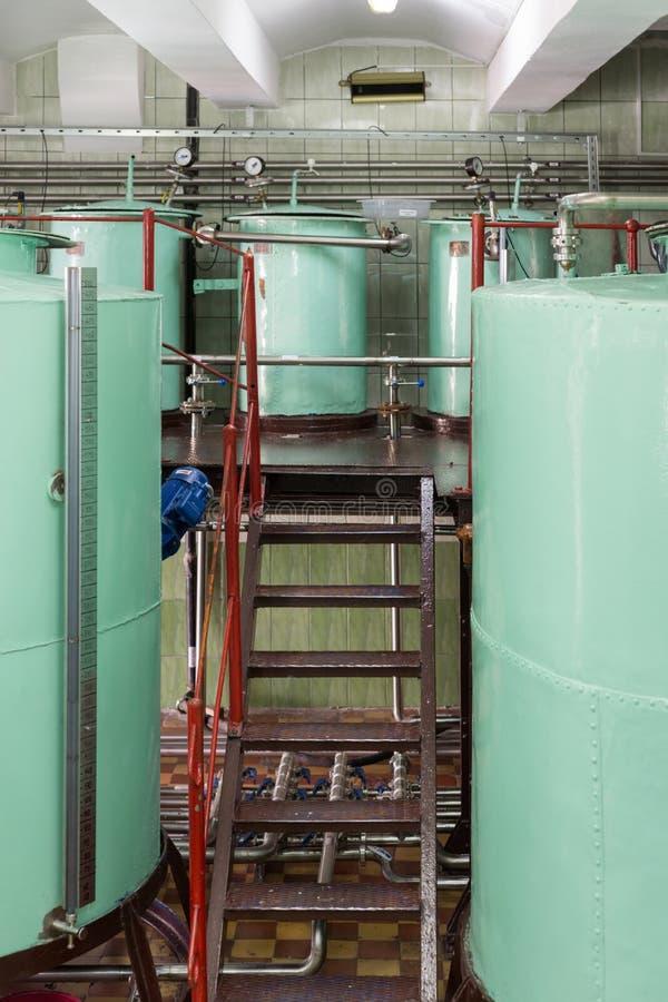 Grandes reservatórios metálicos rebitados da luz - cor verde Fabricação de bebidas alcoólicas fotografia de stock royalty free