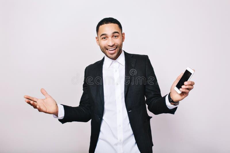 Grandes resultados del logro en el trabajo, éxito en carrera del hombre joven hermoso en la camisa blanca, expresión negra de la  imagen de archivo
