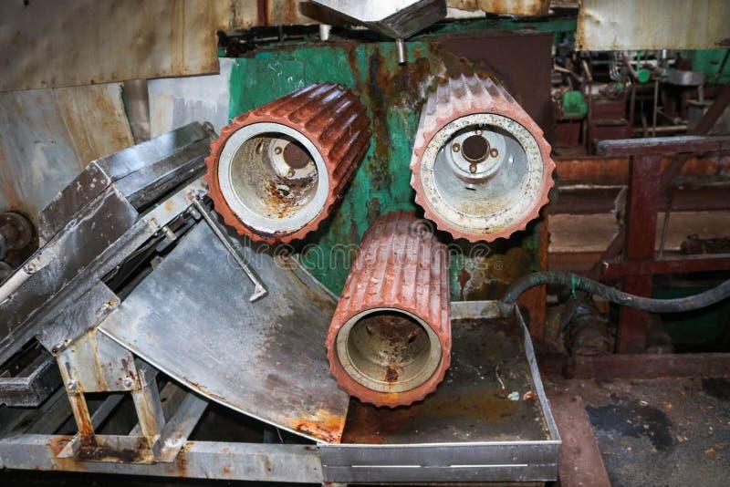 Grandes rolos dos rolos do metal com os dentes das engrenagens da linha de produção, uma correia transportadora na oficina em um  fotos de stock