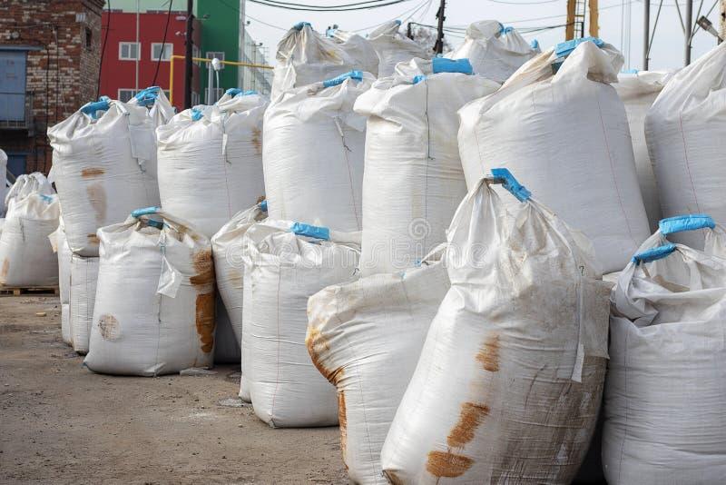 Grandes sacos brancos da mentira de sal na rua Os adubos industriais s?o armazenados nos sacos em um mont?o Manchas oxidadas fotografia de stock royalty free