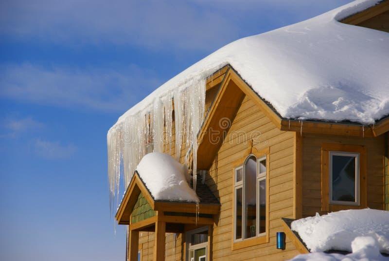 Grandes sincelos em Townhouses após a tempestade de neve pesada imagens de stock royalty free