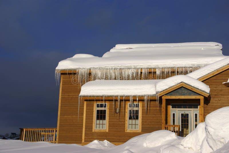 Grandes sincelos em Townhouses após a tempestade de neve pesada fotos de stock