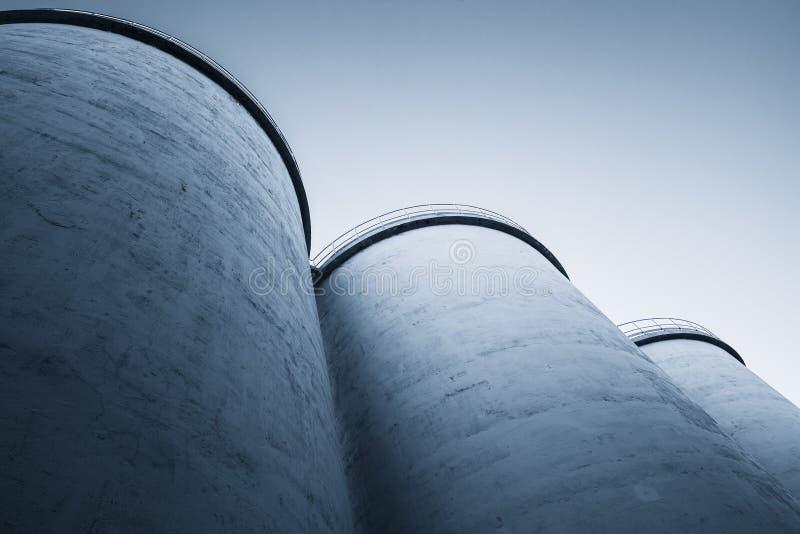 Grandes tanques de silos, foto tonificada azul fotos de stock royalty free