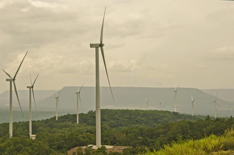 Grandes turbines de vent dans la forêt verte sur la montagne photographie stock libre de droits