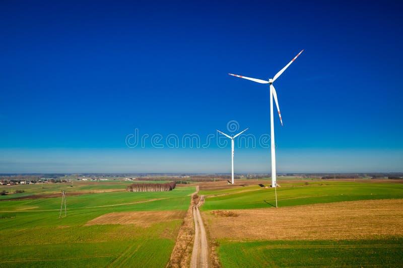 Grandes turbines de vent en tant qu'énergie de substitution sur le champ vert photo libre de droits