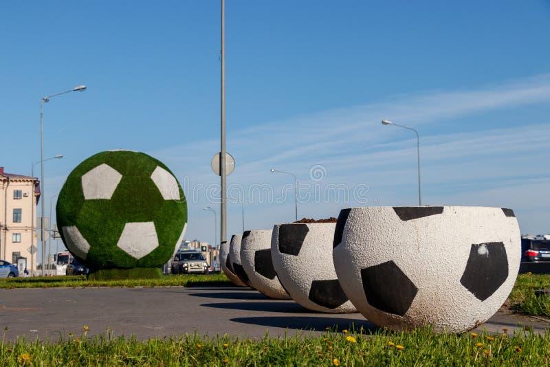 Grandes vasos na forma de uma bola para o futebol A bola de futebol verde gigante é a decoração da cidade para o campeonato do mu fotos de stock