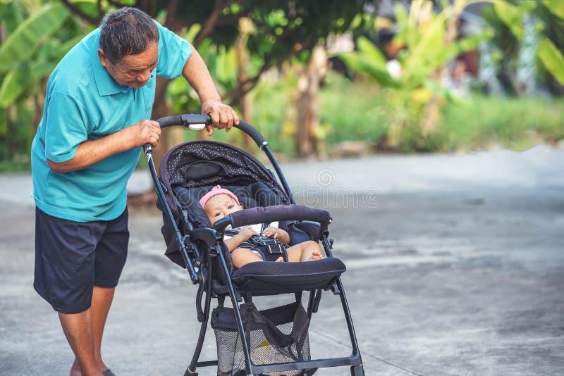 Grandfater pensionato con poca nipote sveglia sul passeggiatore all'aperto immagini stock libere da diritti