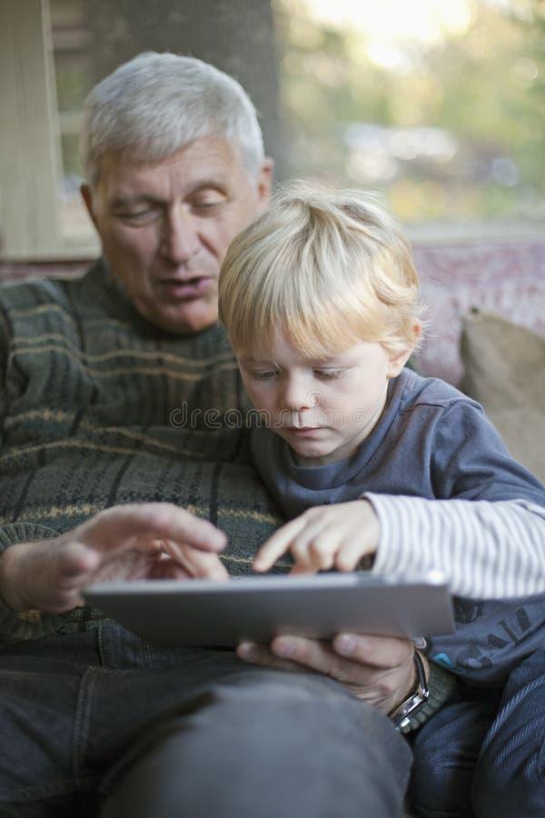 grandfather таблетка ПК внука используя стоковое изображение