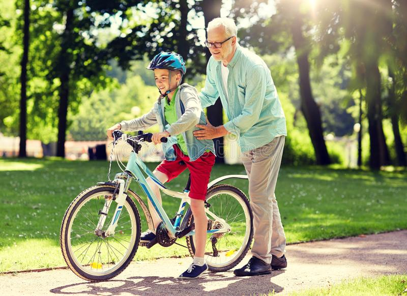 Grandfather and boy with bicycle at summer park stock photos