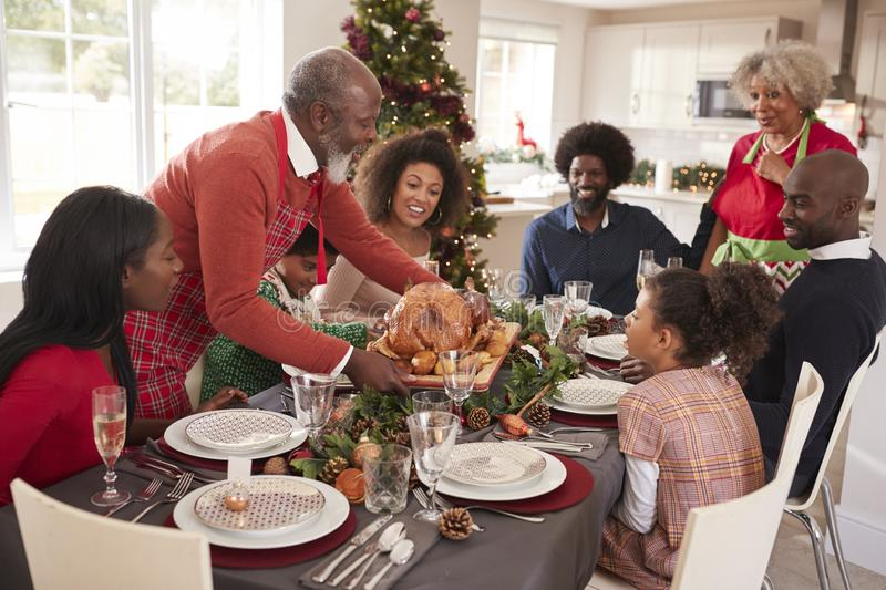 Grandfather bringing the roast turkey to the dinner table during a multi generation, mixed race family Christmas celebration, elev. Ated view stock photo