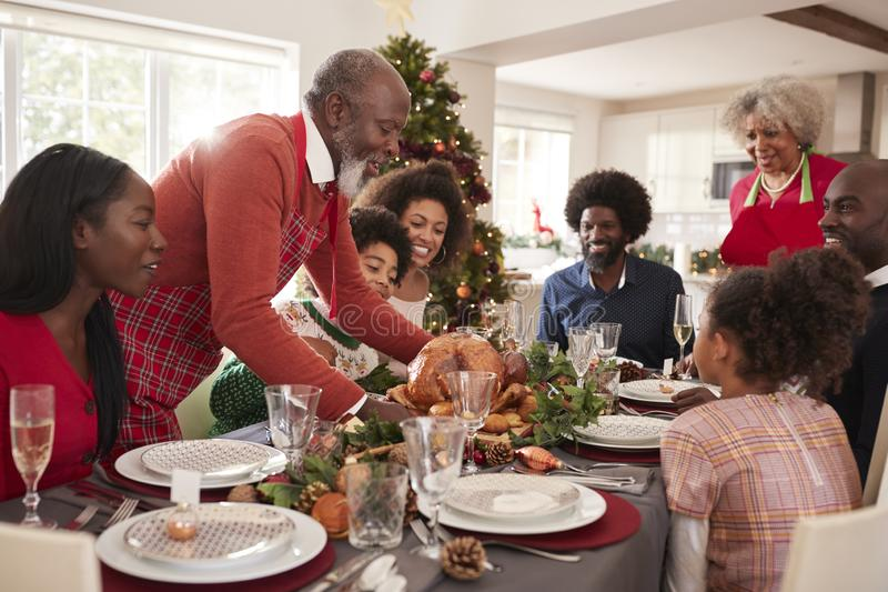 Grandfather bringing the roast turkey to the dinner table during a multi generation, mixed race family Christmas celebration, clos stock image