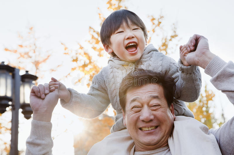 Grandfather Carrying Laughing Grandson on His Shoulders stock photos
