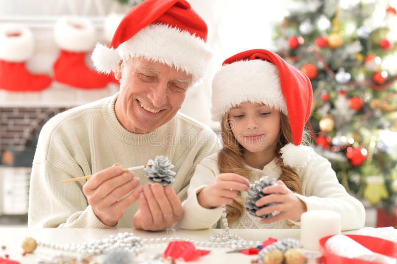 Grandfather and child in Santa hats stock image