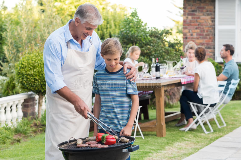 Grandfather cooking with grandson stock image