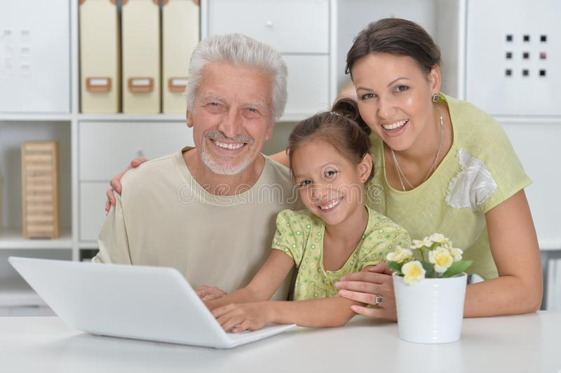 Grandfather, daughter and granddaughter using laptop royalty free stock image