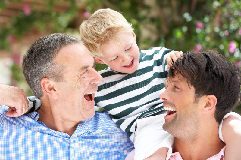 Grandfather And Father Giving Grandson Ride. On Shoulders stock photography