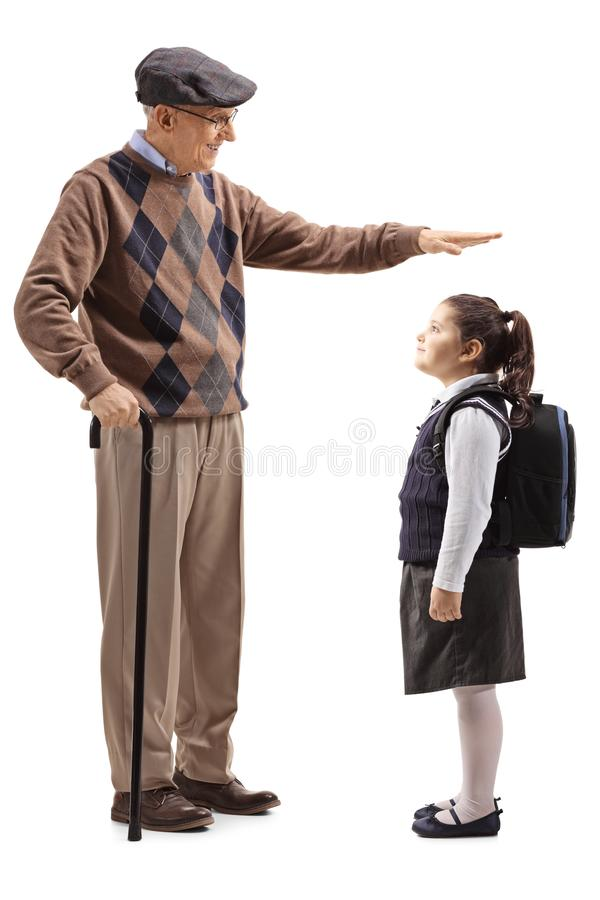 Grandfather gesturing with hand and showing the height of his granddaughter stock images