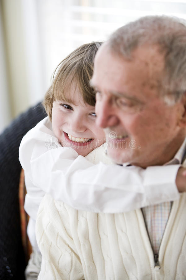 Grandfather getting hug from grandson. Grandfather getting hug from 9 year old grandson, focus on boy royalty free stock photo