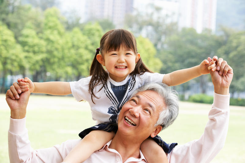 Grandfather Giving Granddaughter Ride On Shoulders