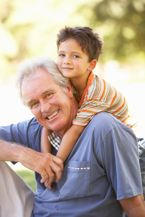 Download Grandfather Giving Grandson Ride On Back In Park Stock Photo - Image: 14639342