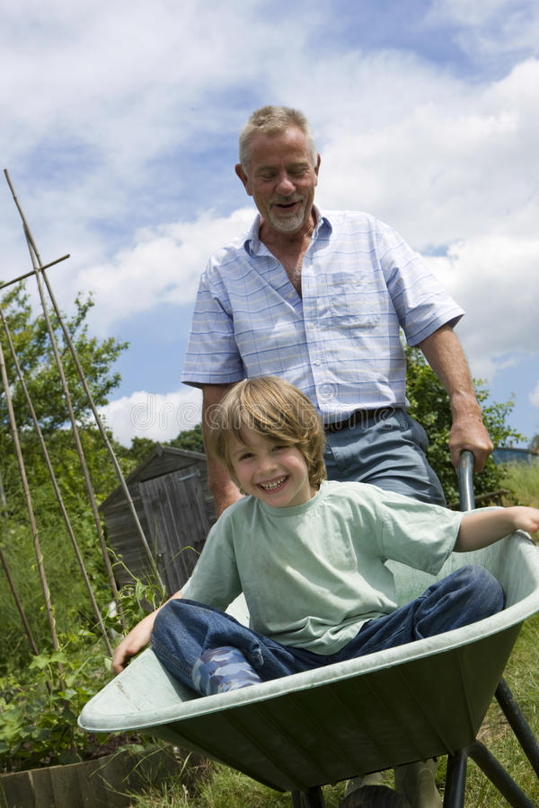 Grandfather Giving Grandson Ride In Wheelbarrow stock images
