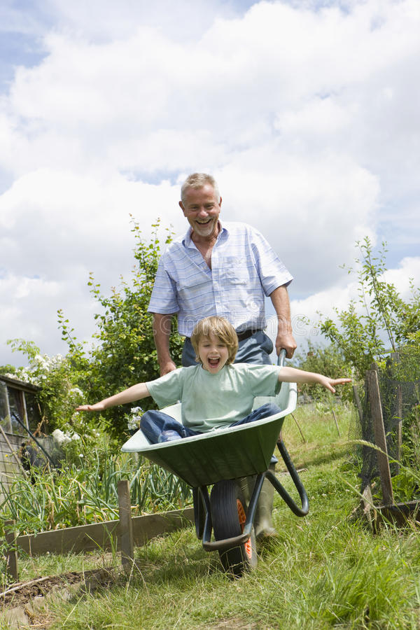Grandfather Giving Grandson Ride In Wheelbarrow stock photo