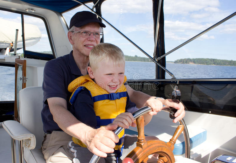 Grandfather and grandchild on adventure. A senior men holds his grandson, wearing a life vest, as they steer a boat from the helm stock image