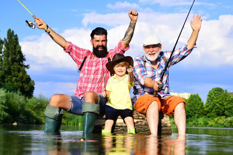 Grandfather and grandchild. Portrait of happy little son, father and grandfather - three generations of men fishing on royalty free stock photography