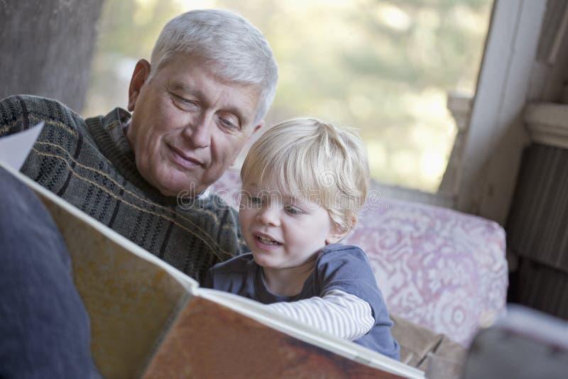 Grandfather and grandchild reading stock photos