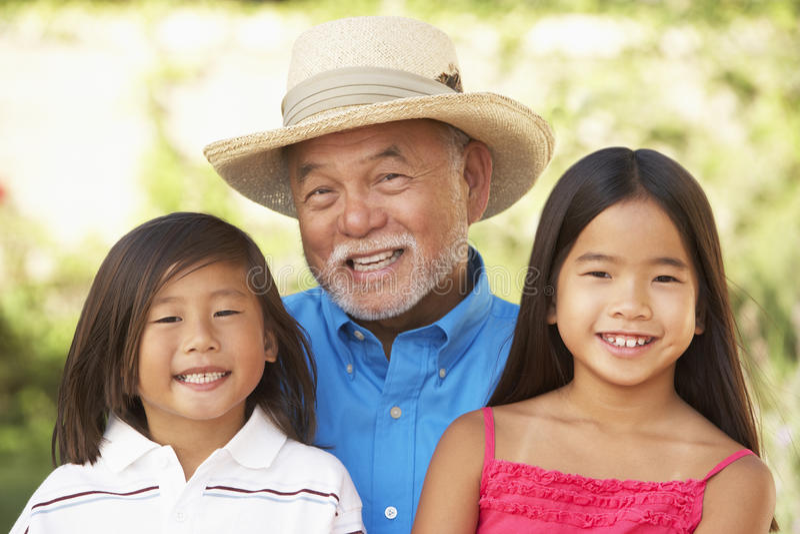Grandfather With Grandchildren In Garden stock photo