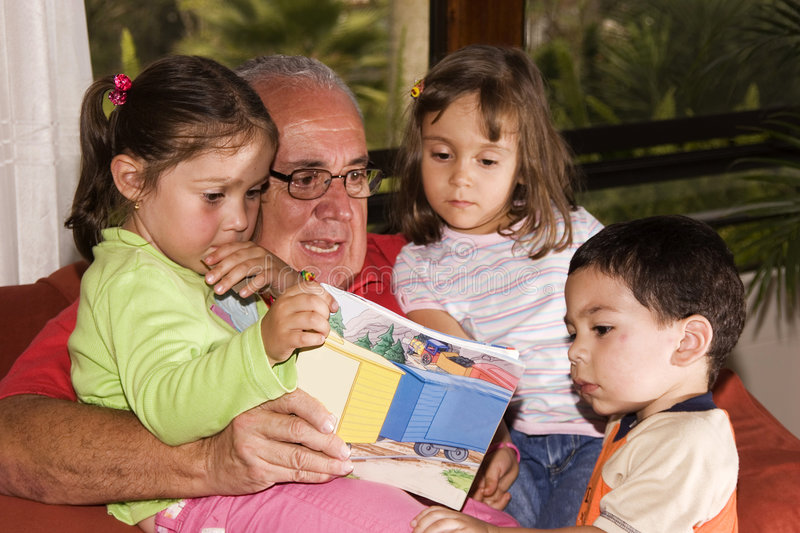 Grandfather and grandchildren reading together royalty free stock photos