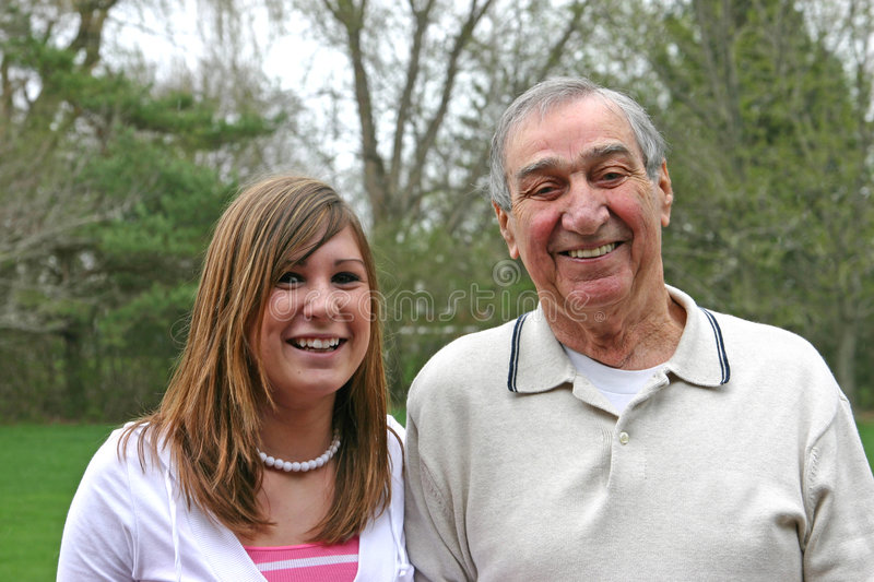 Grandfather with granddaughter. Grandpa laughing with his granddaughter at his side stock image