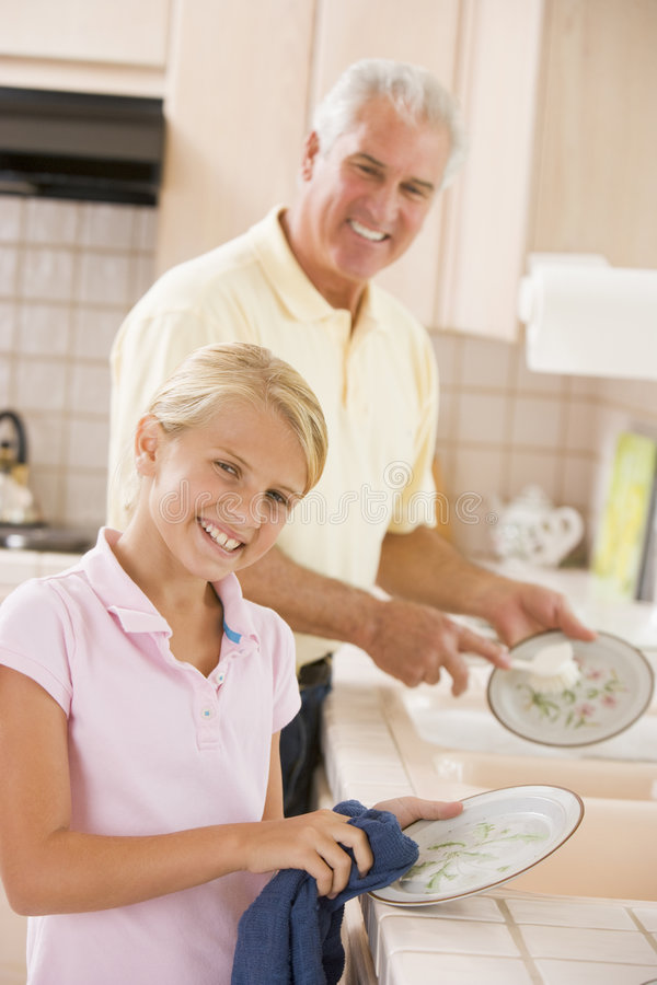 Grandfather And Granddaughter Cleaning Dishes Stock Photo