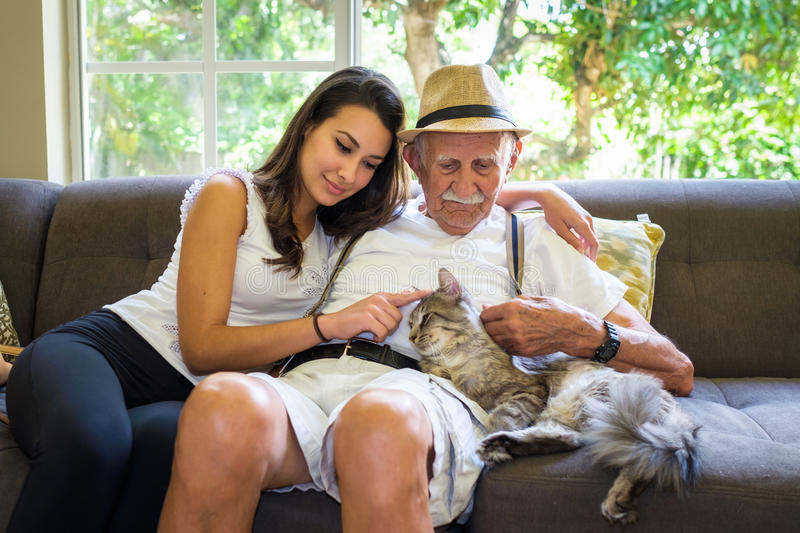 Grandfather and Granddaughter. Elderly eighty plus year old men with granddaughter and cat in a home setting royalty free stock photo