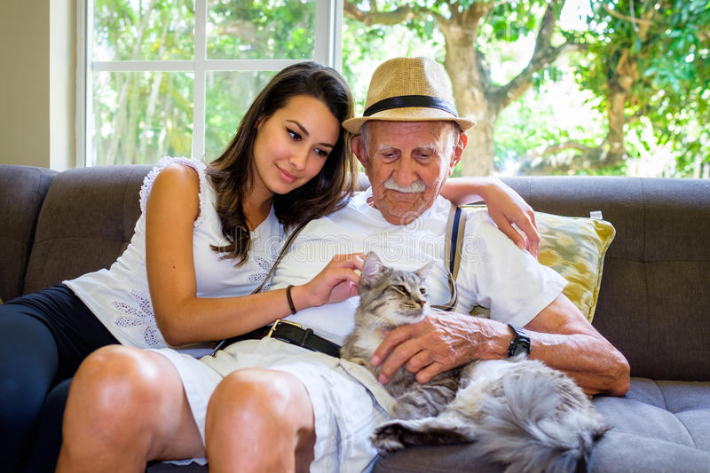Grandfather and Granddaughter. Elderly eighty plus year old men with granddaughter and cat in a home setting royalty free stock photos