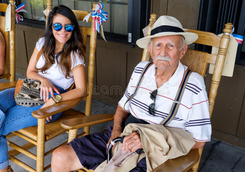 Grandfather and granddaughter. Elderly eighty plus year old grandfather sitting on a rocking chair with his granddaughter stock images