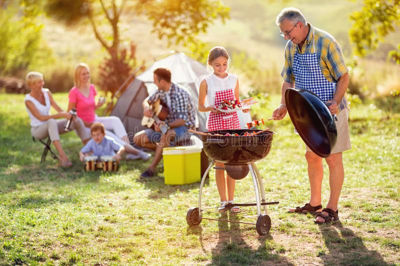 Grandfather and granddaughter making barbeque. For family royalty free stock photos