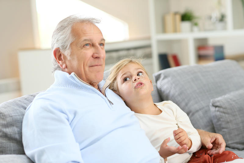 Grandfather with granddaughter in sofa stock images
