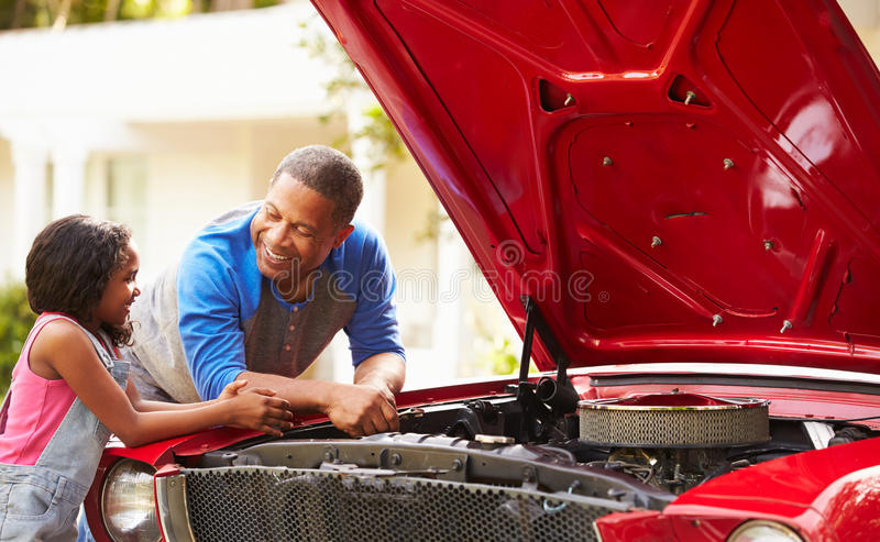 Grandfather And Granddaughter Working On Restored Car royalty free stock photo