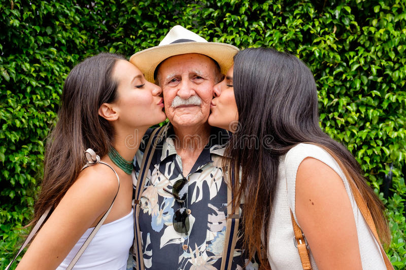Grandfather and Granddaughters. Elderly eighty plus year old men being kissed by his granddaughters in a outdoor setting royalty free stock photo