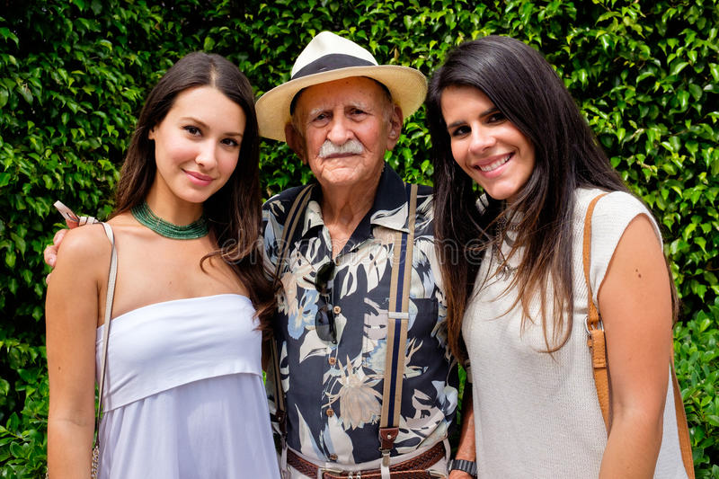 Grandfather and Granddaughters. Elderly eighty plus year old men with his granddaughters in a outdoor setting royalty free stock photo