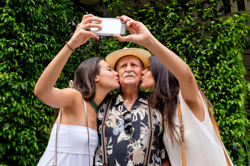 Grandfather and Granddaughters. Elderly eighty plus year old men with his granddaughters taking a selfie in a outdoor setting stock photos