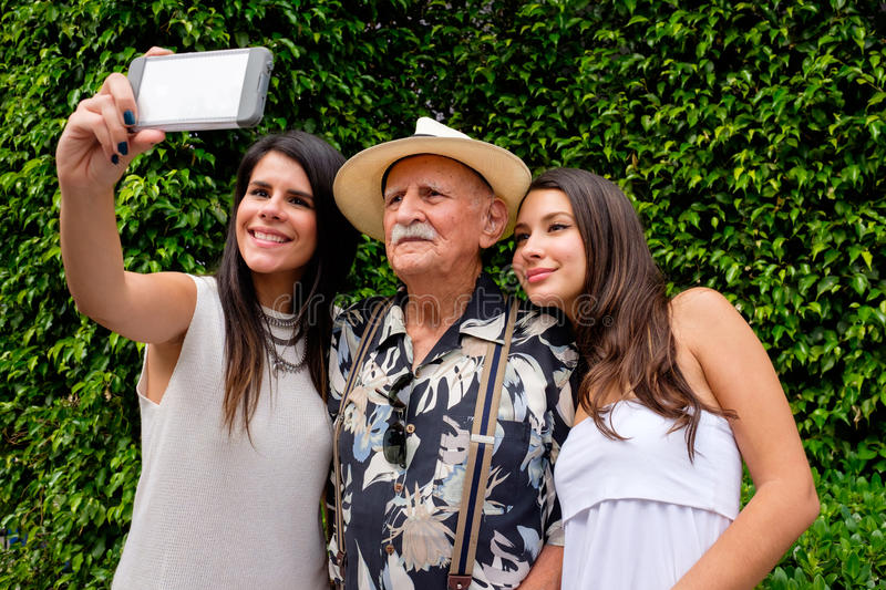Grandfather and Granddaughters. Elderly eighty plus year old men with his granddaughters taking a selfie in a outdoor setting stock photo
