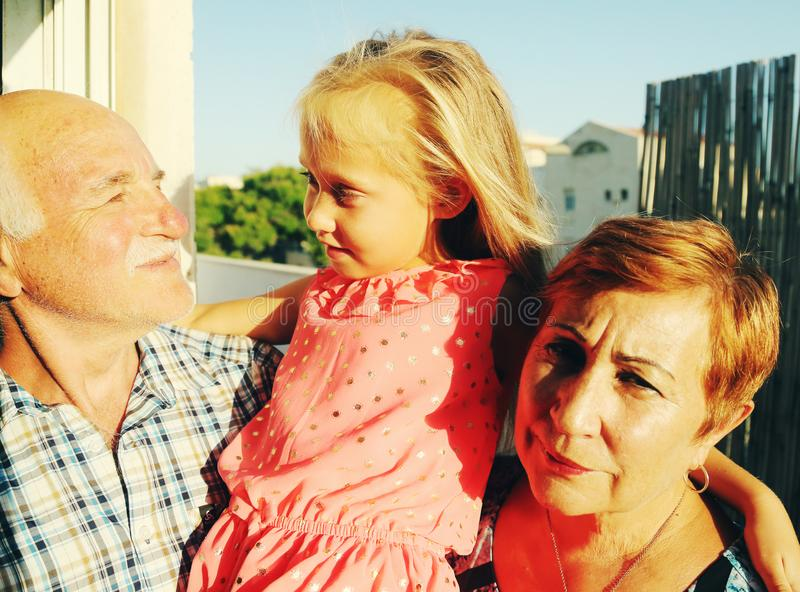 Grandfather and grandmother holding granddaughter royalty free stock image