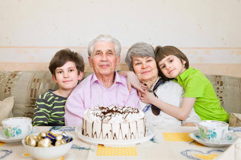Grandfather, grandmother and two brothers are celebrating a birthday royalty free stock photo
