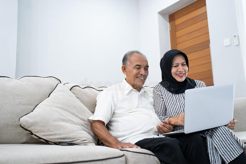 Grandfather and grandmother using a laptop to browsing a place of vacation royalty free stock image