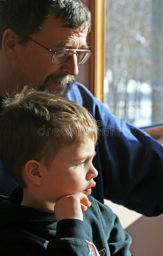 Grandfather with Grandson. This grandfather and his five year old grandson are sitting at a computer monitor researching a subject. This was taken in January royalty free stock images