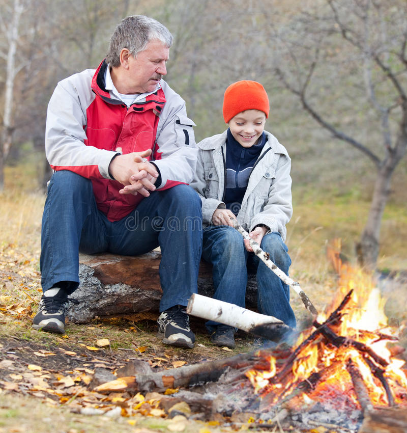 Grandfather and grandson. Around a campfire in the woods royalty free stock images
