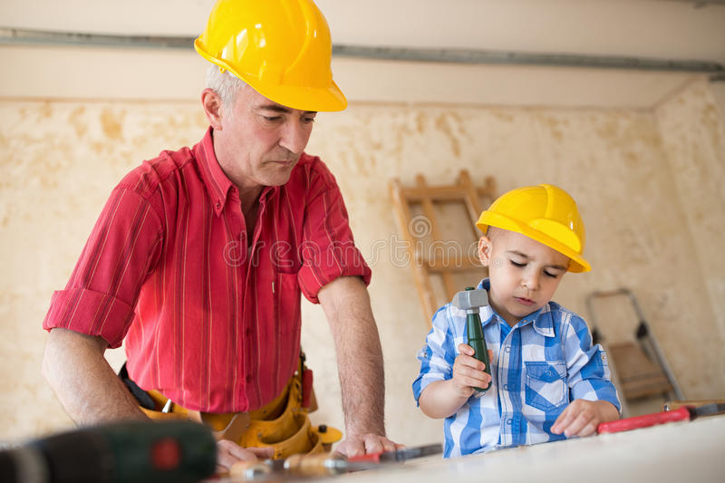 Grandfather and grandson as a dream team in the workshop royalty free stock photo